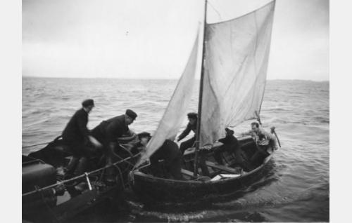 Pirtukanistereja lastataan moottoriveneestä purjeveneeseen edelleeenkuljetusta varten.