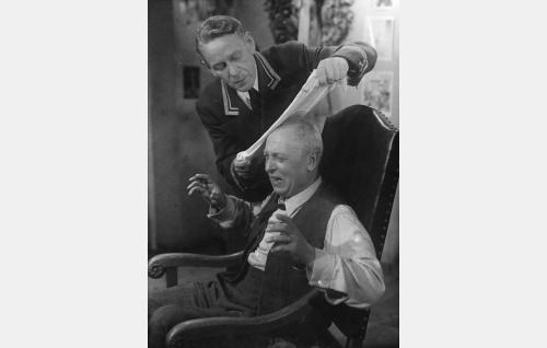 Vahtimestari Teppo (Arvo Lehesmaa) yrittää lievittää kabareeteatterin johtajan Amundus Mielosen (Arvi Tuomi) päänsärkyä.