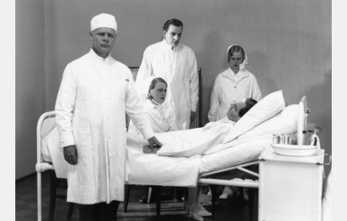 Heikki Huhtamäki (Kaarlo Angerkoski, vuoteeessa) on kuollut keuhkotautiin. Vasemalla parantolan ylilääkäri Wiljam Ania (Eero Kilpi), sairaanhoitaja Helmi Hirvinen (Helena Koskinen), lääkäri Antti Ahonen (Jalmari Rinne) ja sairaanhoitajatar (tunnistamaton).