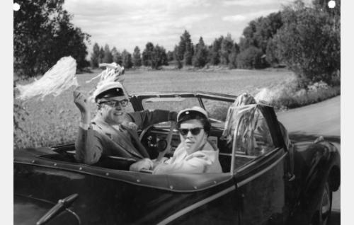 Yhteiskoulun rehtori Kuusi (Tauno Palo) ja hänen opettajakollegansa Ansu (Kirsti Ortola) vappuajelulla Backaksen maisemissa.