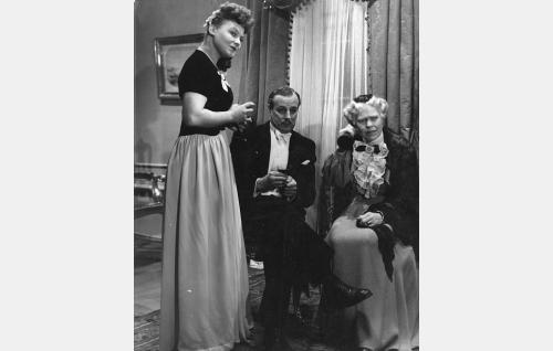 Seisomassa kihlajaisvieras (Rauha Rentola), istumassa sulhanen Arne Melin (Thure Bahne) ja Musteri (Elsa Turakainen).