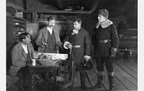 Poliisi (Armas Fredman) ja Simo (Einar Rinne) kuulustelevat laukkuryssiä (Karl Fager ja Eero Kilpi). Fager oli myös elokuvan lavastaja ja Fredman kuvausryhmän jäsen.