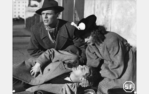 Maassa makaa Vilho Raimola  (Topi Ruuth), häntä auttavat Alf Randell (Leif Wager) ja Inari Mäkinen (Marjatta Uski).