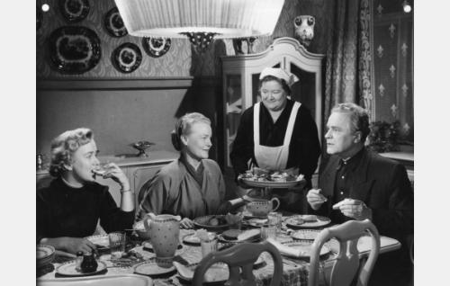 Junkkerin perhettä aterialla. Istumassa vasemmalta Päivi (Elina Pohjanpää), Helena (Emma Väänänen) ja Jari Junkkeri (Eino Kaipainen). Seisten tarjoilee emännöitsijä Anna (Irma Wickström).