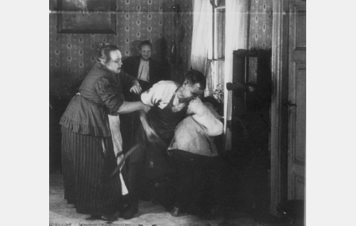 Suutarimestari Simolin (Erkki Karu) antaa Ollille (Alfred Idström) ruumiillista kuritusta, hänen vaimonsa (Kirsti Suonio) yrittää estellä. Taustalla  virnuilee tyytyväinen Simolinin Janne (Uuno Kantanen).
