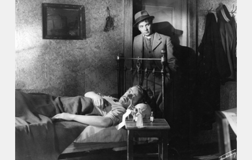 Ovensuussa J. Alfred Tanner (Sakari Halonen), vuoteenomana hänen huonetoverinsa (Aarne Laine).