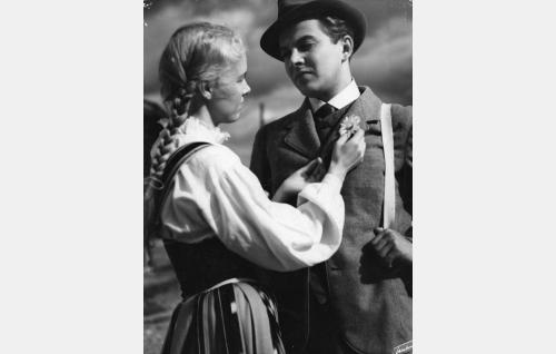 Milda (Eija Inkeri) kiinnittää päivänkakkaran J. Alfred Tannerin (Sakari Halonen) rintaan.
