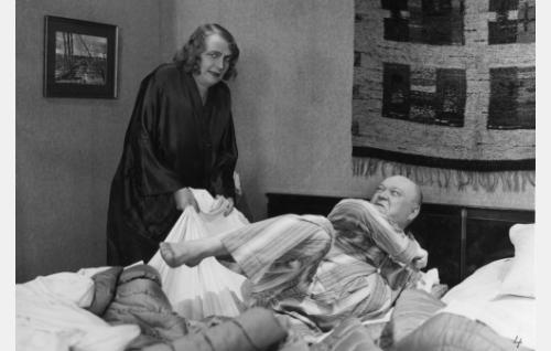 Rouva Keinänen (Hilja Jorma) vie lakanan miehensä (Heikki Välisalmi) alta, sillä perheessä on koittanut pyykkipäivä.