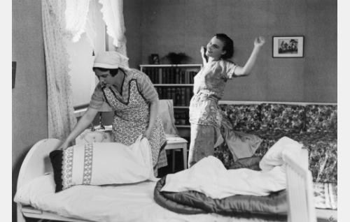 Palvelijatar Mari (Siiri Palmu) kerää liinavaatteet pestäväksi Keinäsen perheen Elsä-tyttären (Ellen Parviainen) huoneesta.