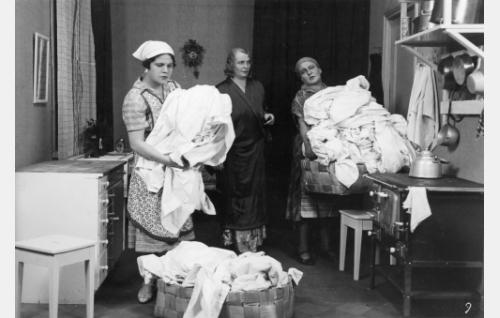 Pyykkäri (Kaija Suonio) noutaa pestävät liinavaatteet rouva Keinäseltä (Hilja Jorma, keskellä) ja palvelijatar Marilta (Siiri Palmu).