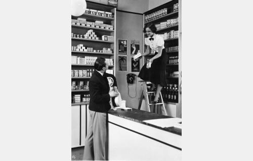 Rohdoskaupan myyjätär (Martta Kontula) esittelee Havin tilauselokuvassa yhtiön tuotteita häneen ihastuneelle Kallelle (Kaarlo Angerkoski).