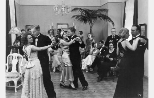 Elsa (Ellen Parviainen) ja Jaakko (Eero Eloranta) romanttisissa tunnelmissa tanssiaiskutsuilla. Heidän vieressään seisomassa palmun edessä Laila Richter.