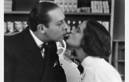 Kalle (Kaarlo Angerkoski) ja hänen mielitiettynsä, rohdoskaupan pikku myyjätär (Martta Kontula) sulavat suudelmaan.