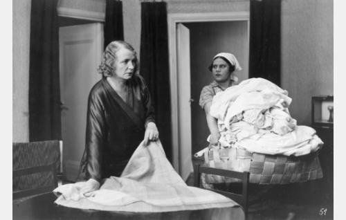 On pyykkipäivä: rouva Keinänen (Hilja Jorma) ja palvelijatar Mari (Siiri Palmu) kokoavat pestävät.