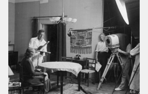 Georg Malmstén ohjaa ja lyö klaffia. Pöydän ääressä istuu Hilja Jorma, kuvaaja Theodor Luts on kätkeytynyt kameran taakse kuvaajansametin suojaan. Paidanhihansa käärinyt mies on tunnistamatta.