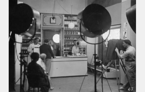 Elokuvan rohdoskauppajaksoa kuvataan. Kameran takana on Theodor Luts, tähtäimessä Kaarlo Angerkoski ja Martta Kontula. Heidän vasemmalla puolellaan on ohjaaja Georg Malmstén ja oikealla puolellaan toisen kameran vieressä studiopäällikkö Armas Fredman. Vasemmalla istuu valkotakkinen naamioija Hannes Kuokkanen.