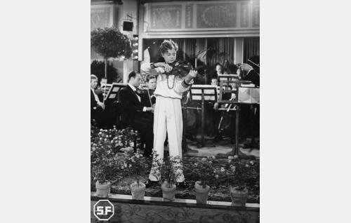 Olavi (Heimo Haitto) antaa ensikonserttinsa Suomessa. Orkesteria johtaa Boris Sirpo. Kuvaus suoritettiin Heimolan talon suuressa salissa.