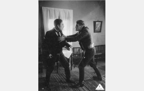 Jussi (Oiva Soini) nousee ruoskaa heiluttavaa vallesmannia (Thorild Bröderman) vastaan. Bröderman esitti saman roolin vuoden 1936 äänielokuvaversiossa.