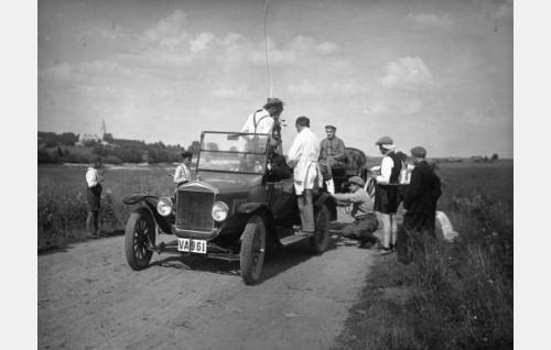Ulkokuvausta Alahärmässä: Einar Rinne istuu vanginpuvussa auton perään kiinnitetyillä rattailla. Kameran ääressä lippalakkipäinen kuvaaja Frans Ekebom, selin valkotakkinen ohjaaja Jalmari Lahdensuo. Kyyryssä auton vieressä kuvausapulainen Armas Fredman ja hänestä oikealle polvihousuinen apulaisohjaaja Martti Tuukka. Taustalla vasemmalla Alahärmän kirkko.