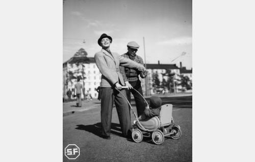 Taiteilija Lasse Kimalainen (Leo Lähteenmäki) ja Jopi (Joel Rinne), rattaissa Nappe (Seppo Ellenberg).