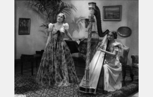 Musiikkiesitys kutsuilla: laulajana Tuli Arjo, harpun ääressä rouva Juvonen.