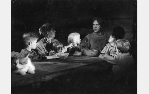 Korpiloukon väri aterialla. Vanhemmat Riika (Liisa Nevalainen) ja Topi (Holger Salin) sekä heidän lapsensa Vesteri (Jukka Eklund, vas.), Pirjeri (Tiina Jokela), Petti (Marianne Eronen), Iita Linta Maria (Terhi Virtanen) ja Sake (Pertti Tanner).