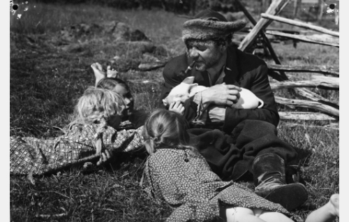 Putkinotkon vuokralainen Juutas Käkriäinen (Matti Lehtelä) sylissään porsas ja ympärillään piirissä myötäpäivään perheen tyttäristä Sanukka (Pirjo Paatso), Esteri (Leena Rahikka) ja Repekka (Raija Suomalainen).