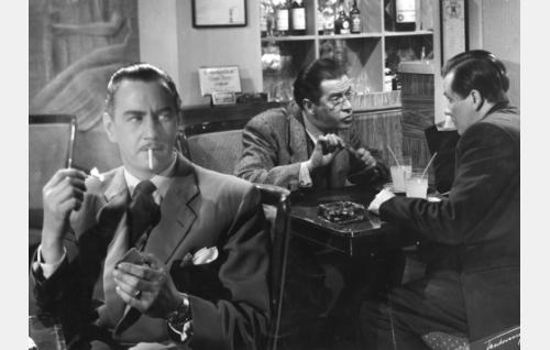 """Robins, """"Mr. Knickerbocker"""" (Kunto Karapää) kuulee Tornin baarissa Leo Laakson (Kaarlo Halttunen) ja Toivo Teräsvuoren (Hannes Häyrinen) mielenkiintoisen keskustelun."""