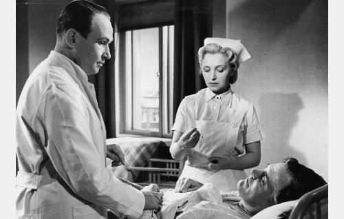 Tohtori Heinonen (Leo Riuttu) ja sairaanhoitaja Leena Auer-Lepistö (Ansa Ikonen) hoitavat majuri Yrjö Harttia (Tauno Palo).