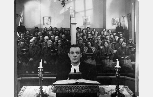 Etualalla Jalmari Rinne vankilapastorina, miesten puolella eturivissä lähimpänä väliseinää Edvin Laine ja Aku Korhonen, naisvankien puolella vastaavasti Mervi Järventaus.