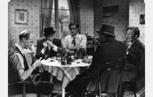 Korttipöydän ääressä Severi (Esa Pakarinen), Rovaniemen Hanski (Jorma Nortimo), Vuotuan Ville (Veikko Uusimäki), Mikko (Kalle Rouni, selin) ja Julle (Jorma Ikävalko).