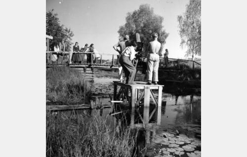 """""""Praktikaapeli""""-teline on pystytetty keskelle jokea Limingassa. Kameraan kurkistaa ohjaaja Ilmari Unho, hänen vasemmalla puolellaan seisoo pipopäinen kuvaaja Uno Pihlström ja oikealla kamera-assistentti Niilo Heino."""