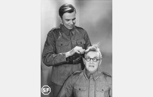 Alokas Lauri Auermaa (Leo Lähteenmäki) komppanian parturin (Olavi Suominen) käsittelyssä.