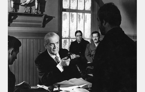 Jooseppi Kenkkunen (Heimo Lepistö, selin) on joutunut käräjille. Tuomarina Paavo Jännes, lautamiehinä ikkunan ääressä Armas Jokio ja Hannes Veivo.