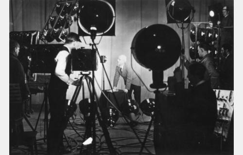 Yrjö Nyberg ohjaa kameran takana seisten. Kameran ja näyttelijän välissä näkyy jalustalla seisova mikrofoni. Etuvalon vieressä Aaro Helmisalo, hänestä oikealle käsi lampun jalustassa Kurt Vilja ja oikealla ylhäällä Karl Perón suuntaamassa lamppua. Keskellä kirkkaassa valaistuksessa mikrofonin vieressä näyttelijä Thure Wahlroos.