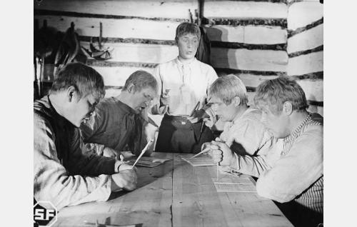 Eero (Arvo Kuusla) opettaa veljiään lukemaan. Pöydän ääressä vasemmalta Lauri (Unto Salminen), Aapo (Kaarlo Kytö), Tuomas (Eino Kaipainen) ja Juhani (Edvin Laine).