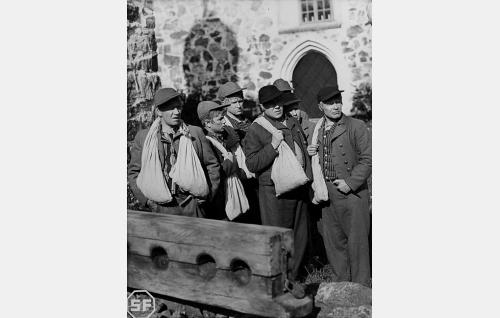 Veljekset Nurmijärven kirkolla jalkapuun ääressä. Timo (Joel Rinne, vas.), Eero (Arvo Kuusla), Aapo (Kaarlo Kytö), Juhani (Edvin Laine), Lauri (Unto Salminen), Simeoni (Kaarlo Kartio) ja Tuomas (Eino Kaipainen).