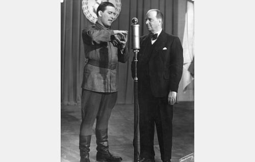 Ilmari Linnamaa (Henry Theel) leikkii pikku Pirkkoa Markus-sedän (Markus Rautio) juontamassa radiolähetyksessä. Menossa on Hämä-hämähäkki.