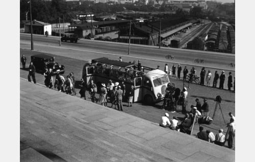 Kuvausryhmä Eduskuntatalon edustalla. Filmauskamera on turistibusssin nokan kohdalla, kuvan oikeassa laidassa jalustalla mainosvalokuvaajan kamera.