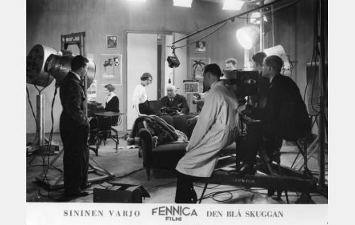 Kameran kuva-alassa mikrofonin alla Bigi Nuotio ja Heikki Välisalmi, heistä oikealle valkotakkinen äänittäjä Yrjö Nyberg (selin), kameran toisella puolen kasvot päin valokuvaajaa kamera-apulainen Karl Perón ja selin ohjaaja Valentin Vaala sekä kuvaaja Oscar Lindelöf.