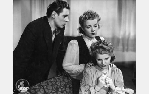 Istumassa Marja (Aija Vilanto), sohvan takana hänen ystävättärensä Vilma (Ulla Polviander) ja tämän poikaystävä Leo (Esko Saha).