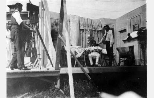 Erkki Karu (oik.) valmistautuu riepottamaan korituolissa istuvaa Väinö Lehmusta. Vasemmalla kuvaaja Frans Ekebom kameroineen.