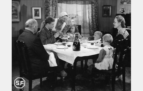 Suomisen perhe aterialla. Vasemmalta myötäpäivään isä (Yrjö Tuominen), Olli (Lasse Pöysti), Hilda (Siiri Angerkoski), Pipsa (Maire Suvanto), Matti (Martti Saarikivi), äiti (Elsa Turakainen) ja Marja (Seija Saarikivi).