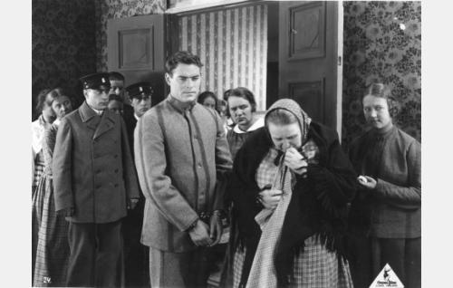 Miestaposta epäilty Ojelmiston Eero (Oiva Soini) on raudoissa. Käräjäyleisön joukossa on toisena vasemmalta nuori nainen (Elli Ylimaa) ja etualalla silmäkulmaansa pyyhkivä Sanni Ylänen (Kirsti Suonio).