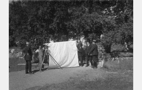 Kuvausvalmisteluja Nummen kirkkotarhan portilla. Kameran vieressä kuvaaja Raoul Reynols, hänestä vasempaan ohjaaja Konrad Tallroth, äärimmäisenä oikealla päänäyttelijä Oiva Soini.