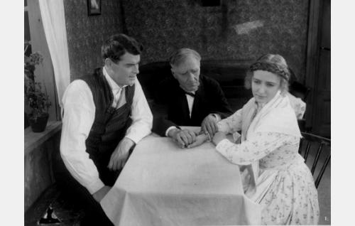 Ojelmiston Eero (Oiva Soini) ja hänen nuori vaimonsa Elsa (Heidi Blåfield-Korhonen). Keskellä istuu Elsan Tuomas-isä (Edvin Stenström).