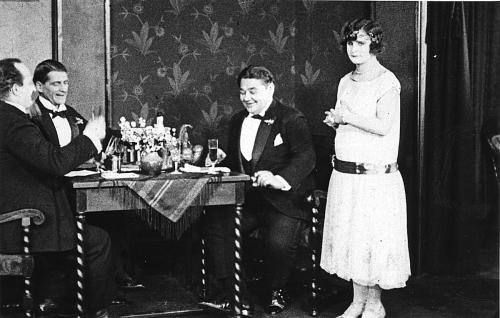 Iloinen pöytäseurue taiteilija von Bjelken ateljeessa: vasemmalta Erkki (Paavo Costiander), Martti (Yrjö Somersalmi) ja kunnallisneuvos Kanto (Volmar Neiro), oikealla seisoo Hilkka Kanto (Maire Heide).