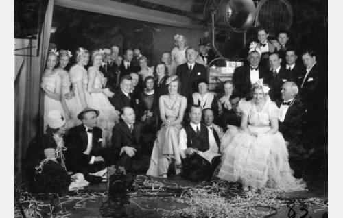 Sanomalehtimiehiä ja Syntipukin tekijöitä yhteiskuvassa Stockmannin vintillä. Eturivissä toisena vasemmalta istuu Ossi Korhonen, ensimmäisenä balettitytöistä oikealle silmälasipäinen Pekka Lönngren. Kuvan keskellä istuu Ester Toivonen ja hänen takanaan seisoo kirjailija Agapetus, Toivosen oikealla puolella istuvat lattialla Erkki Karu ja Carl Fager, oikealla istuu Mary Hannikainen Artturi Järviluoman sylissä. Järviluoman takana seisoo frakkipukuinen Georg Malmstén. Kampaaja Hellä Laiho kurkistaa miesten keskeltä takarivissä vasemmalta. Muut henkilöt ovat tunnistamatta.