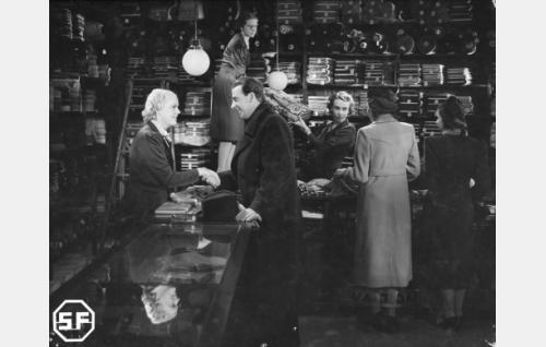 Myyjätär Emmi Hytönen (Kaisu Leppänen, vas.) ja Lehtori Aarre Einola (Joel Rinne) tapaavat kangaskaupassa. Muut henkilöt ovat todennäköisesti Ilma Hämäläinen, neiti Järvinen, Harriet Ingelius ja Ina Kajander.
