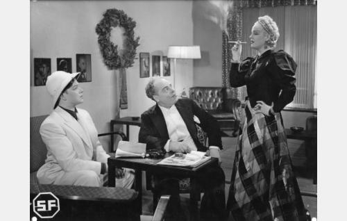 Vasemmalla näyttelijä Aarne Uusitalo (Unto Salminen) rooliasussaan. Hänen vieressään teatterinjohtaja Alfons Kukkaketo (Toppo Elonperä) ja seisomassa näyttelijätär Irma Aaltonen (Kaisu Leppänen).